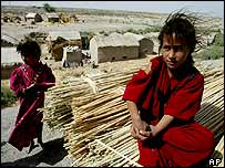 Iraqi girls sit need a stack of reeds, Basra