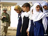 Iraqi schoolgirls walk past an American soldier