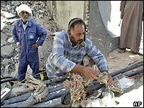 Iraqi engineer repairs telephone line in Baghdad