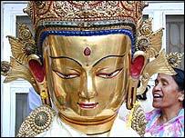 Mujer junto a m�scara budista.