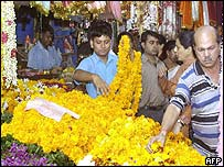 A Hindus select garlands of marigolds at a flower stall in Delhi