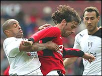 Ruud van Nistelrooy is hounded by Fulham defender Alain Goma (left)