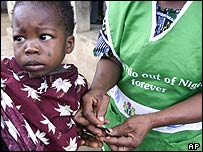 A child has his thumb painted with ink to show he has been immunised