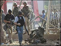 US Army special forces arrive to examine the remains of a suicide car at the scene of an attack in Baghdad