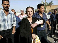 An injured woman is led away from the scene of the Red Cross bombing, 27 October 2003