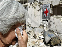 Woman wipes her eyes as she walks past destroyed International Committee of the Red Cross building in Baghdad