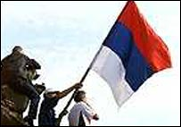 Demonstrators wave a Serbian flag as Milosevic's reign ends