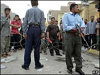 Iraqi police stand guard as Baghdad residents queue for work