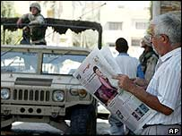 Baghdad man reading a newspaper as a US soldier stands on a truck nearby
