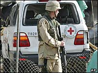 US soldier beside damaged Red Cross vehicle in Baghdad