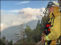Firefighter in Running Springs in the San Bernardino mountains watches as smoke from forest fires