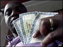 Zimbabwean shows new temporary bank notes launched by the central bank, September 2003