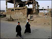 Afghan schoolgirls walk past buildings in Kabul destroyed during war