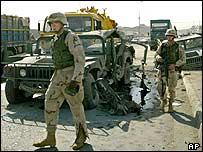 US soldiers pass by destroyed Humvees after an explosion in Mosul, northern Iraq