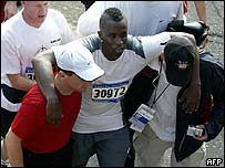 P Diddy being helped after crossing the finishing line in New York on Sunday