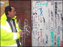 Mr Davies checks out a graffiti-covered wall