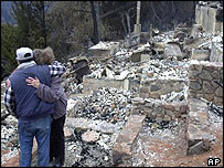 Couple in Cuyamaca, California, hug as they stand in the remains of their own home