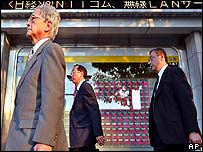 Businessmen walk past a board showing stock prices in Tokyo
