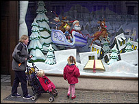 Family looks in the window of a shop featuring Christmas decorations