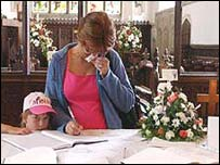 A mourner signs a book of condolence