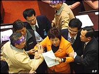 An MP is restrained by colleagues during the debate