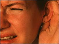 Woman holding ear, Alain Dex/Publiphoto/SPL