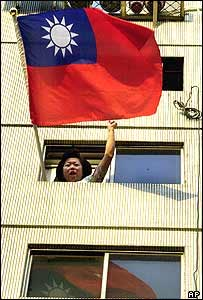 A woman waves the Republic of China flag out of her apartment window