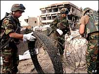 Italian soldiers put up barbed wire round their base in Iraq, which was hit by a suicide bomb