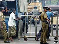 Police oversee workers in Colombo moving barricade to form check-point