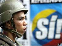 Venezuelan soldier in front of pro-referendum poster