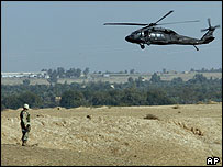 A helicopter flies over the scene of an earlier Black Hawk crash