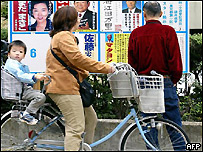 People look at campaign posters  before casting their ballots in Japan's poll
