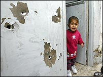Child walks out through a bullet-riddled entrance in Samarra