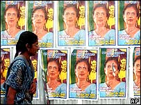 Woman walks past a wall with posters of President Kumaratunga in Colombo