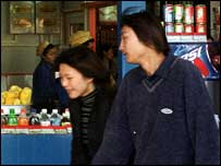 A young couple walk past a soft drinks stall in Beijing