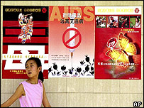Chinese girl walks past Aids poster in Beijing