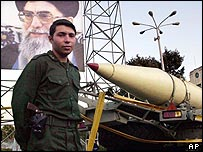 Iranian Revolutionary Guard stands in front of a surface-to-surface Shahab-2 missile, under a picture of supreme leader Ayatollah Ali Khamenei