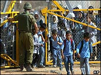 An Israeli soldier lets Palestinian children through a gate in the West Bank security barrier