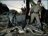 A Saudi policeman walks over the wreckage of the Riyadh bomb, 9 November 2003