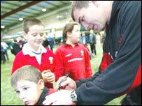 Iestyn Harris signs an autograph for a young fan