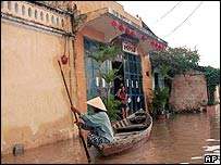 A woman uses a small boat to navigate a flooded street in the ancient town of Hoi An, Vietnam