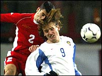 Wales defender Mark Delaney challenges Dmitry Bulykin