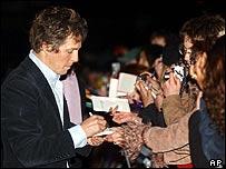 Hugh Grant signing autographs