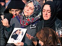 The mother and wife of a Turkish police officer Bulent Bostanoglu killed in the attack pray at his funeral