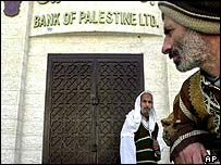 Palestinian men in front of the closed Bank of Palestine