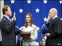 Schwarzenegger (left) is sworn in by Chief Justice Ronald George (right), with the actor's wife Maria Shriver (centre) looking on