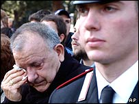 A man wipes tears from his eyes as the funeral takes place