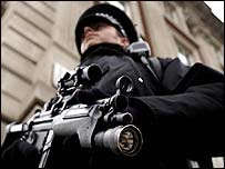 An armed British policeman stands guard outside the US Embassy in London