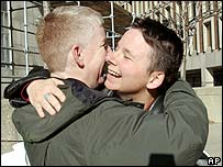 Kim McGinn, left, and Jen Chiasson embrace after the Massachusetts verdict