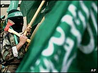 A Hamas militant holds an axe as he stands among Hamas flags